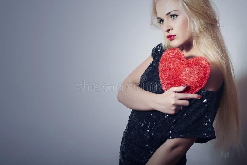 Belle femme blonde avec le coeur rouge. Fille de beauté. Montrez le symbole d'amour. Saint-Valentin. Robe noire photographie stock libre de droits