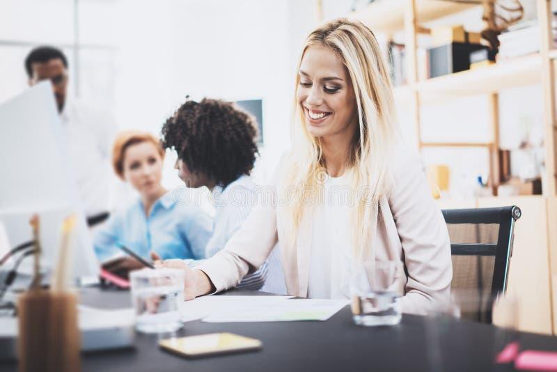 Belle femme blonde collaborant avec des collègues dans le bureau Groupe de quatre collègues discutant le projet d'affaires horizo photographie stock libre de droits