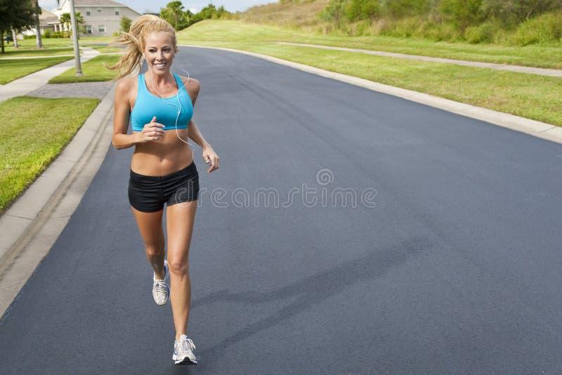 Belle femme blonde courant avec le joueur MP3 images libres de droits