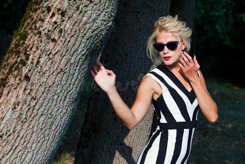 Belle femme blonde dans la forêt d'automne au coucher du soleil photographie stock libre de droits