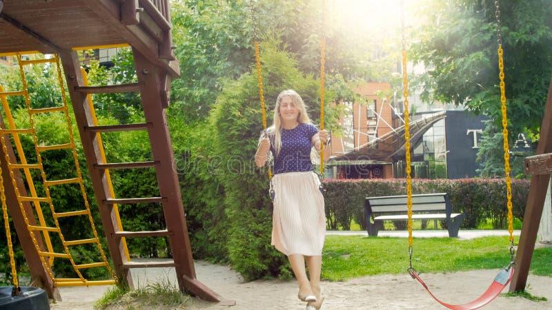 Belle femme blonde dans la longue jupe balançant sur l'oscillation à chaînes au parc photo libre de droits