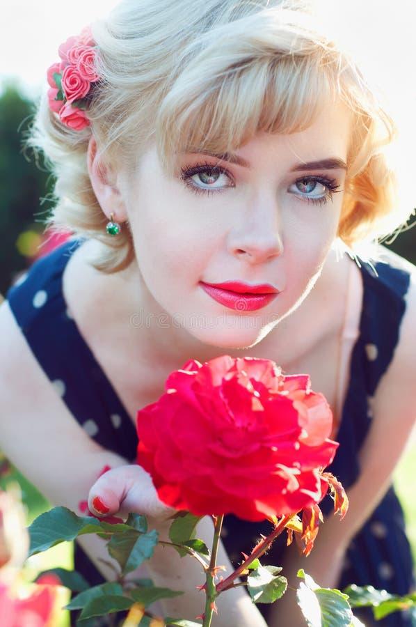 Belle femme blonde dans la robe bleue posant dans le jardin images libres de droits