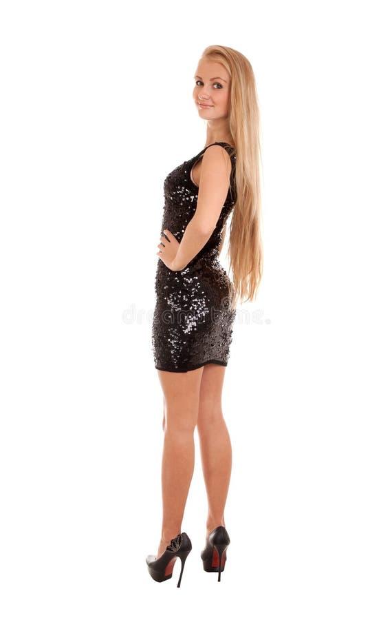 Belle femme blonde dans la robe brillante noire image stock