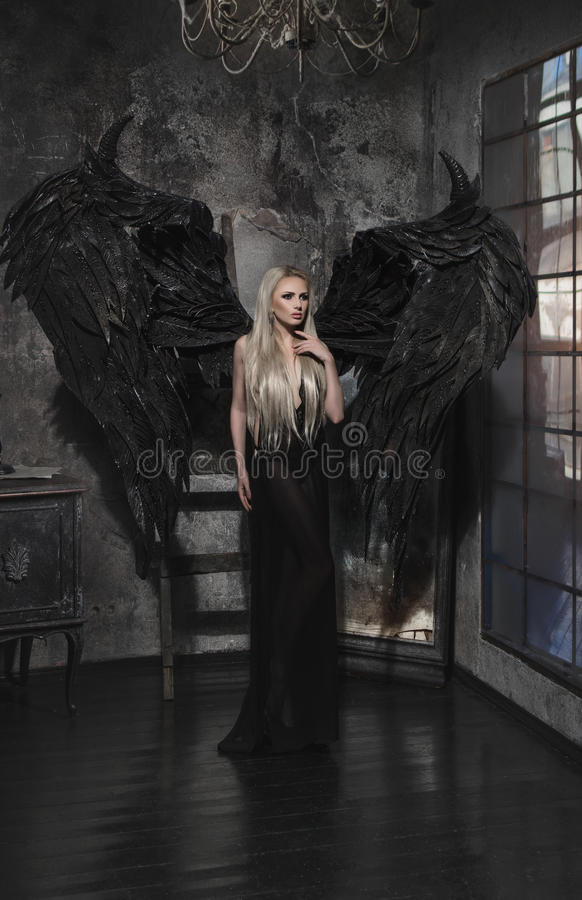 Belle femme blonde dans la robe noire avec des ailes images libres de droits