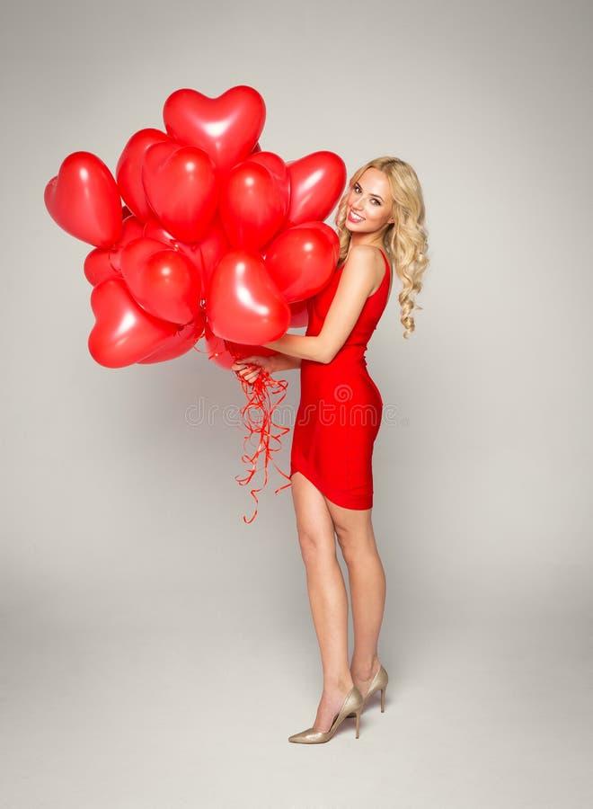 Belle femme blonde dans la robe rouge, tenant le coeur de ballons Jour du `s de Valentine photographie stock libre de droits