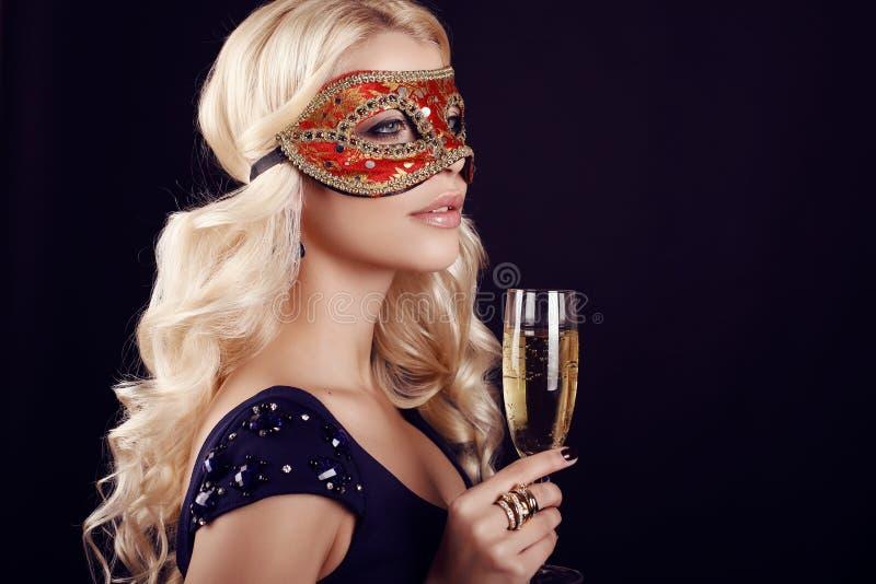 Belle femme blonde dans le masque de carnaval, avec le verre de champagne photo libre de droits