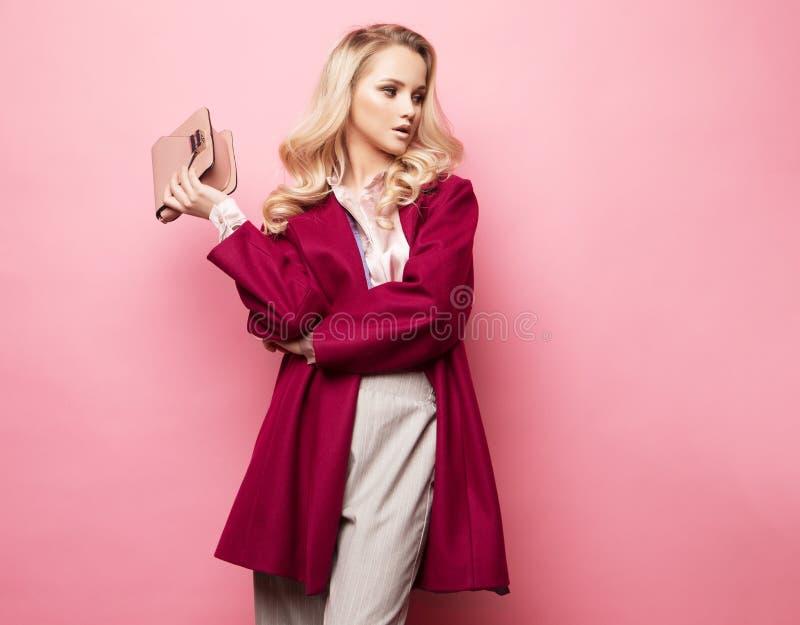 Belle femme blonde dans un chemisier et le pantalon portant des lunettes, tenant le sac à main posant au-dessus du fond rose photos stock