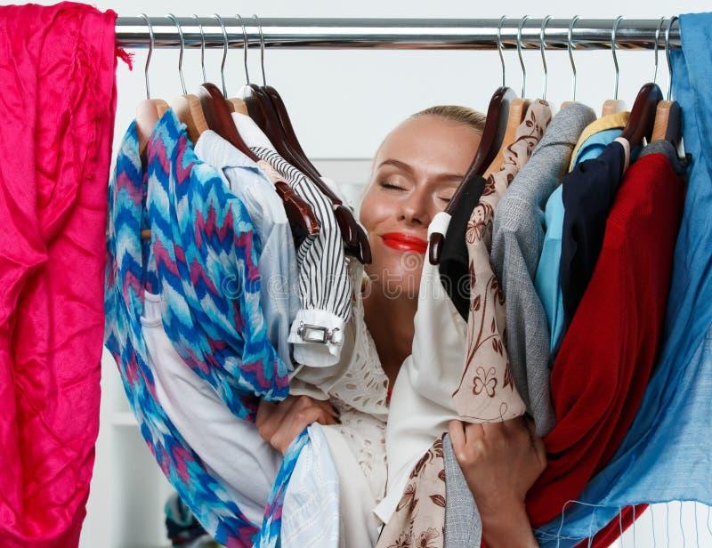 Belle femme blonde de sourire tenant le support intérieur de garde-robe photo stock
