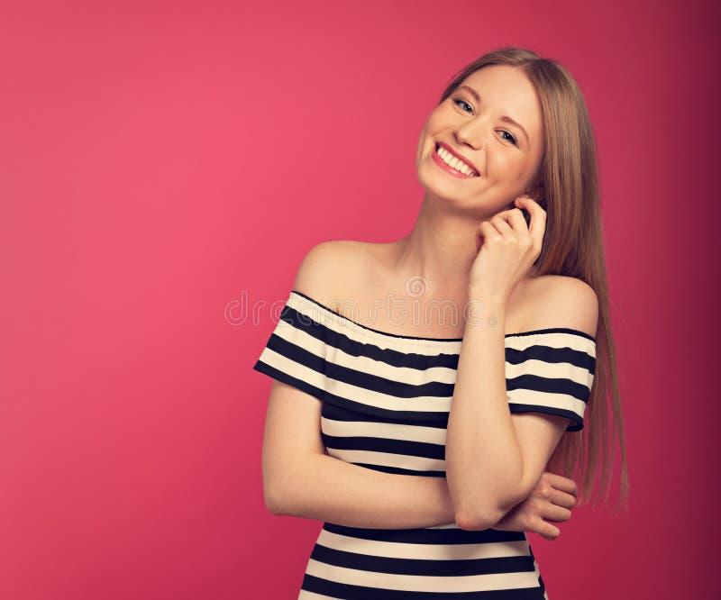 Belle femme blonde de sourire toothy large de positie dans le dre rayé images stock