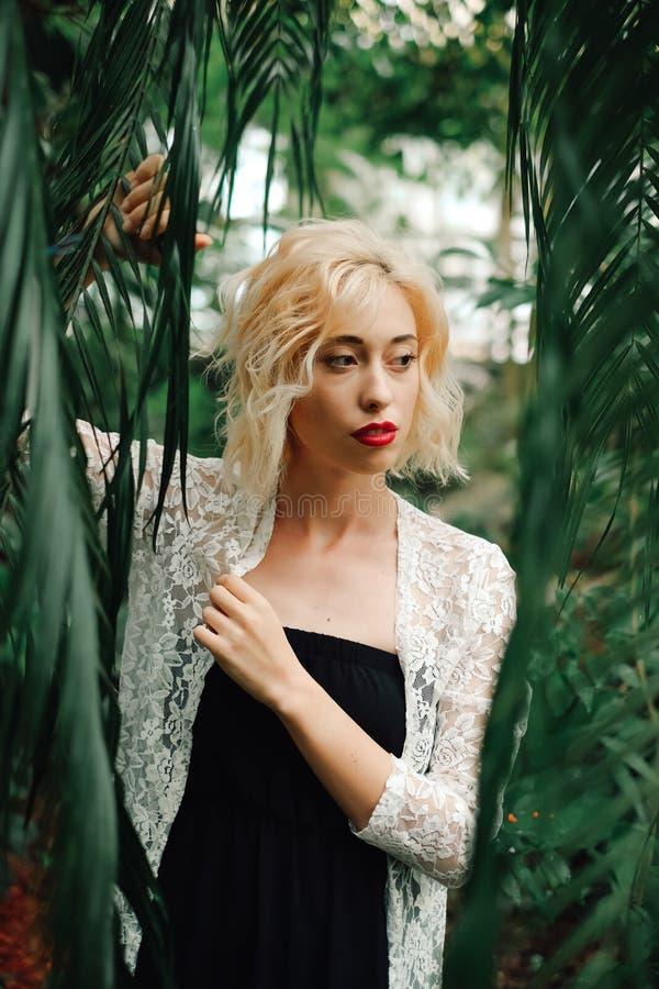 Belle femme blonde posant dans le jardin botanique tropical photographie stock libre de droits