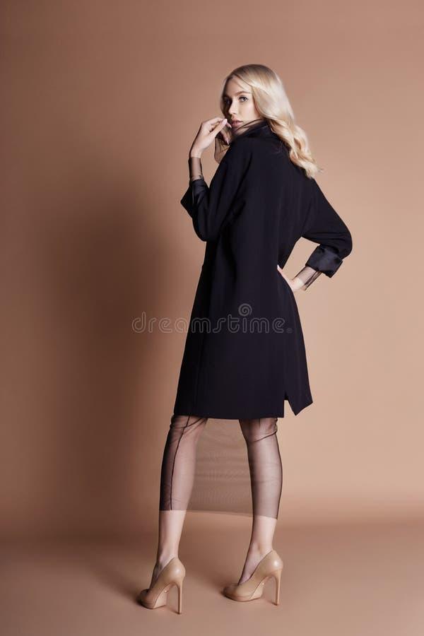 Belle femme blonde posant dans un manteau noir sur un fond beige Habillement de défilé de mode, femme avec le chiffre parfait images libres de droits