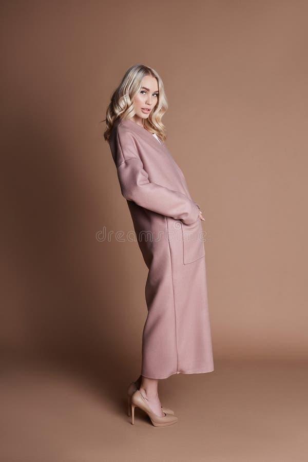 Belle femme blonde posant dans un manteau rose sur un fond beige Habillement de défilé de mode, femme avec le chiffre parfait, lo photographie stock