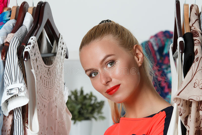 Belle femme blonde réfléchie tenant le support intérieur de garde-robe photographie stock libre de droits