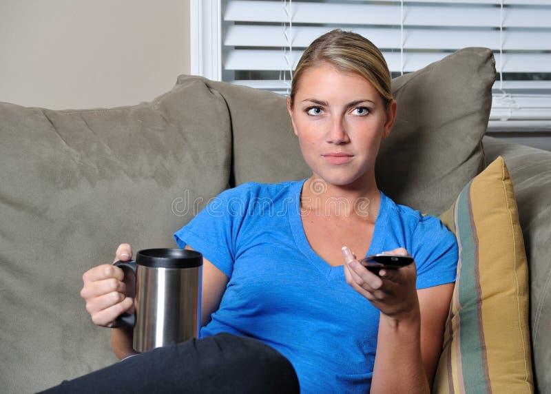 Belle femme blonde regardant la TV avec le distant photos libres de droits