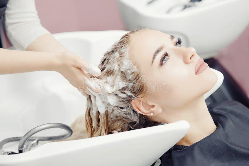 Belle femme blonde se laver les cheveux dans un salon de beauté Massage de la tête de conception images libres de droits