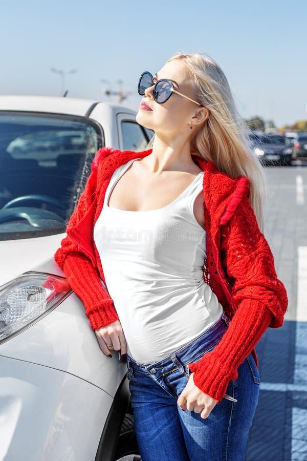 Belle femme blonde se tenant près de sa voiture dans des lunettes de soleil Concentré image libre de droits