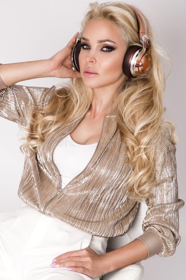 Belle femme blonde sexy avec de longs cheveux et corps parfait dans la robe étonnante avec les cristaux d'or et argentés photo libre de droits