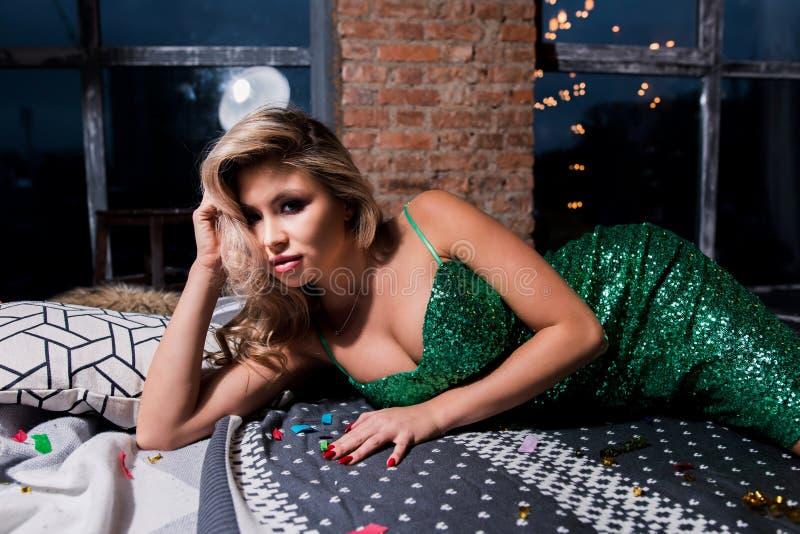 Belle femme blonde sexy dans la robe courte élégante se trouvant sur le sofa moderne Modèle de mode dans la robe d'or Partie, vac photographie stock