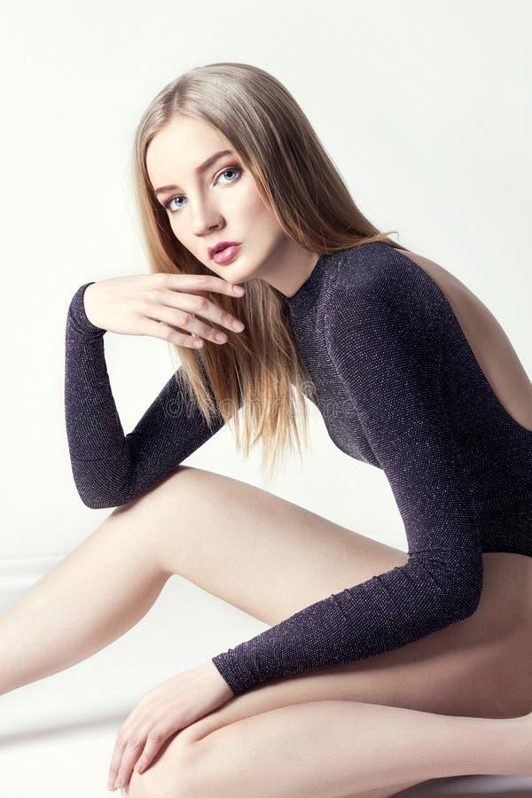 Belle femme blonde sexy Fille avec le corps parfait se reposant sur le plancher Beaux longs cheveux et jambes, peau propre lisse, photographie stock libre de droits