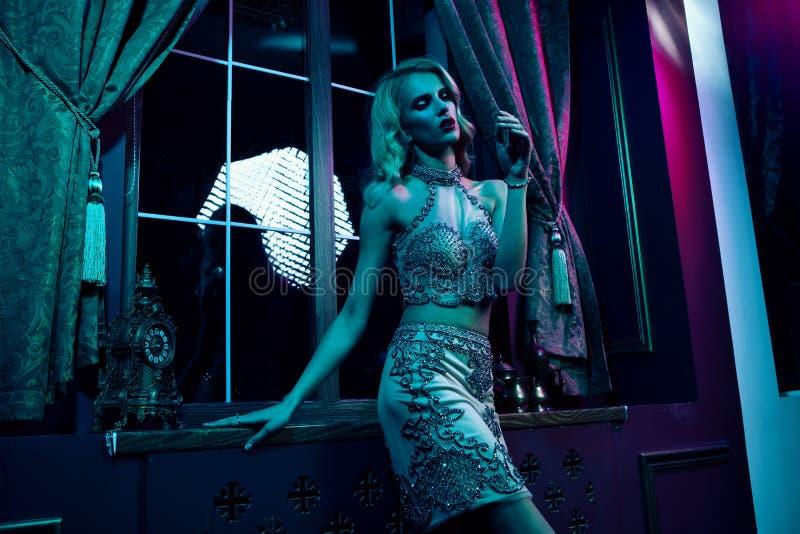 Belle femme blonde sexy sur le fond violet, partie photographie stock libre de droits