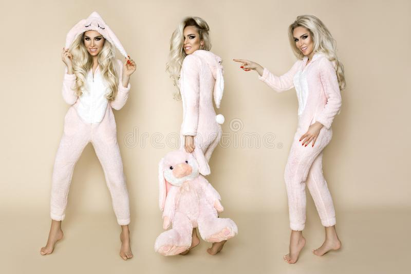 Belle femme blonde sexy utilisant un pyjama, un costume de lapin, souriant heureusement photos stock