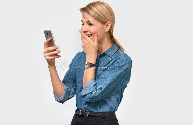 Belle femme blonde stupéfaite, riant et se sentant heureuse à de bonnes nouvelles de lecture, chemise de port de denim, posant su photographie stock