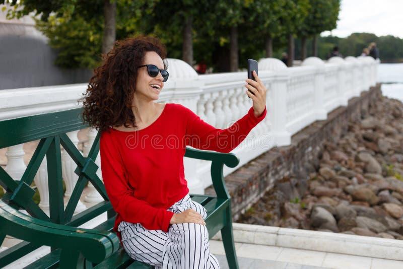 Belle femme bouclée élégante dans des lunettes de soleil faisant le selfie sur un smartphone, posé sur un banc vert en parc photos libres de droits
