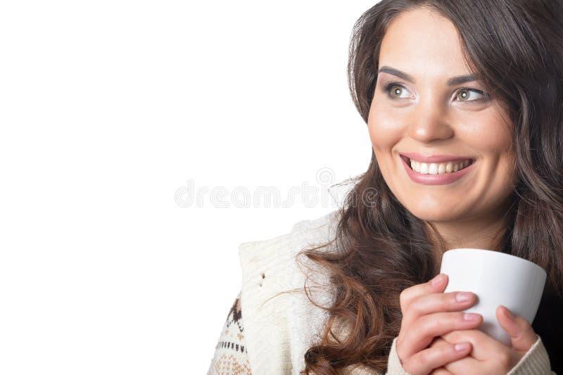 Belle femme bouclée utilisant la tasse chaude de participation d'habillement d'isolement sur le blanc photos stock