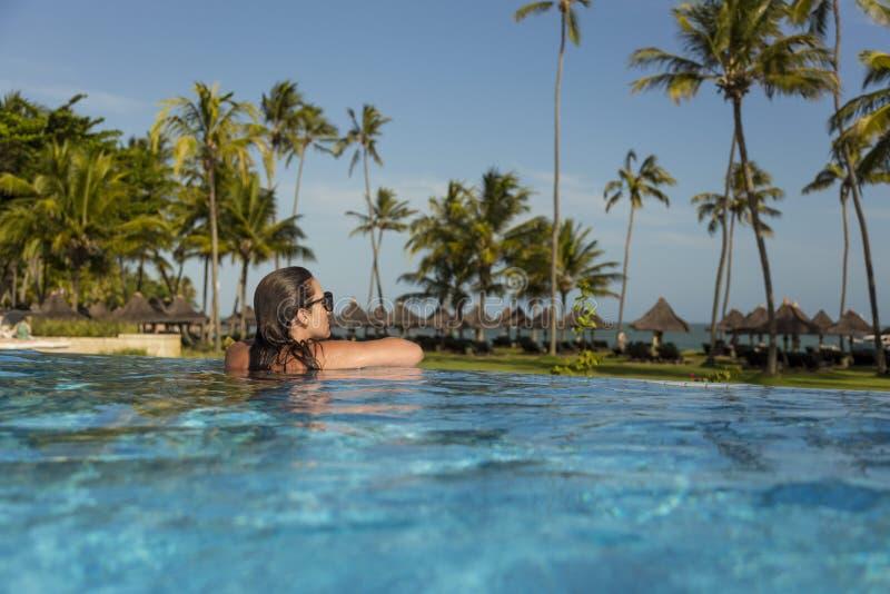 Belle femme brésilienne appréciant des vacances de vacances à une piscine photo stock