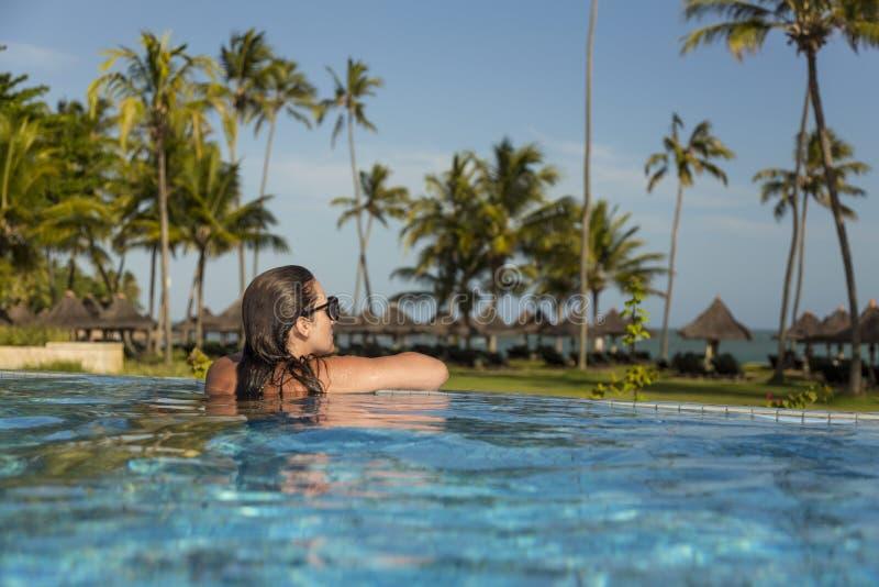 Belle femme brésilienne appréciant des vacances de vacances à une piscine photos libres de droits