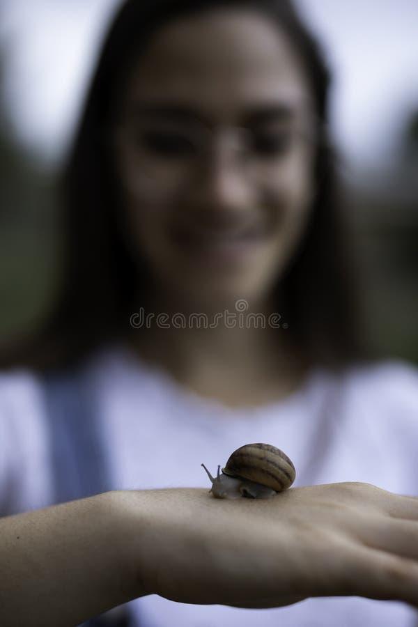 Belle femme brouillée tenant un escargot dans des ses mains dehors photos libres de droits