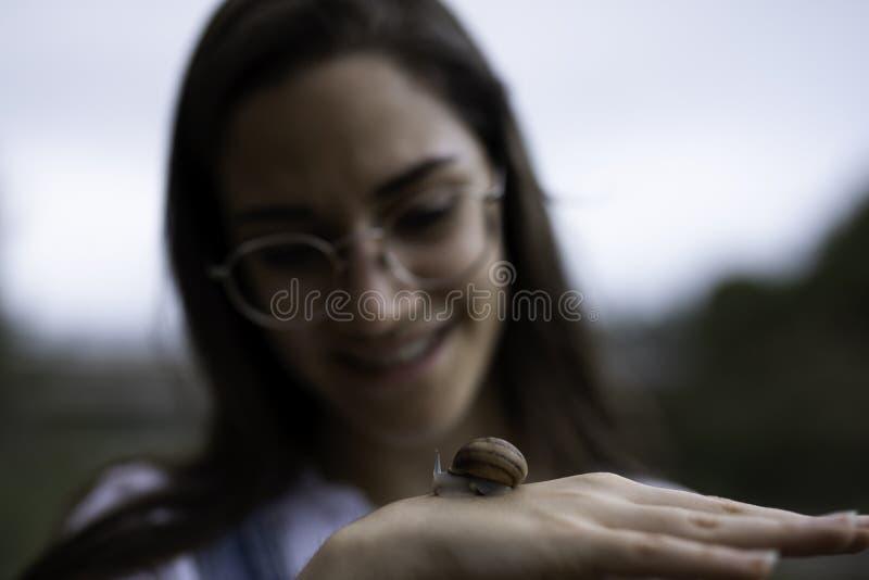 Belle femme brouillée tenant un escargot dans des ses mains dehors photo stock