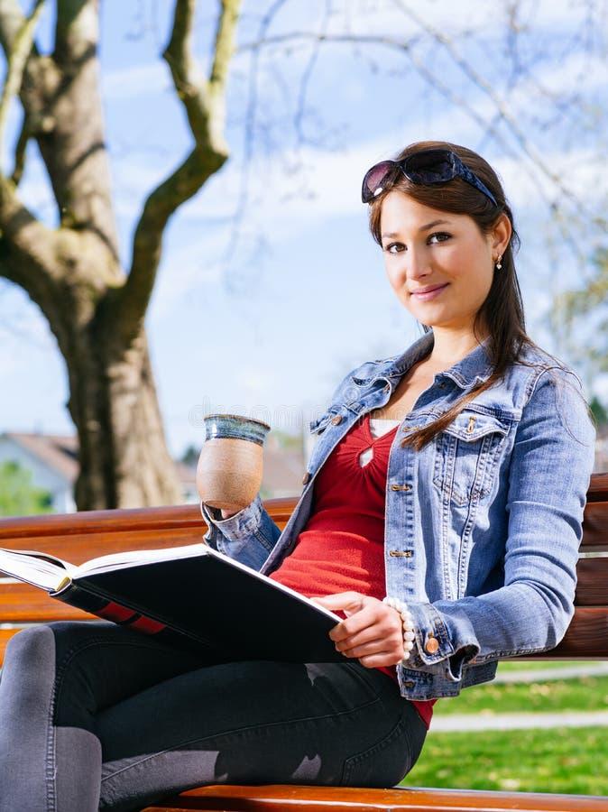 Belle femme buvant et lisant sur le banc de parc photos libres de droits