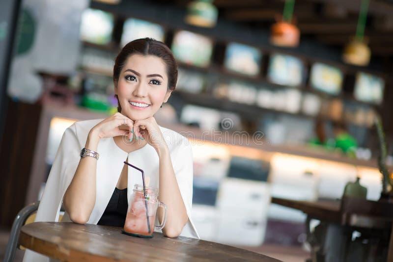 Belle femme buvant la boisson douce en café photo stock