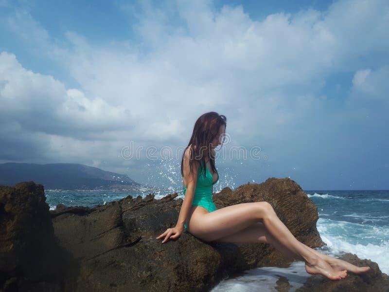 Belle femme caucasienne bronzée se reposant sur la plage de mer de roche Cr?te, Gr?ce photographie stock libre de droits