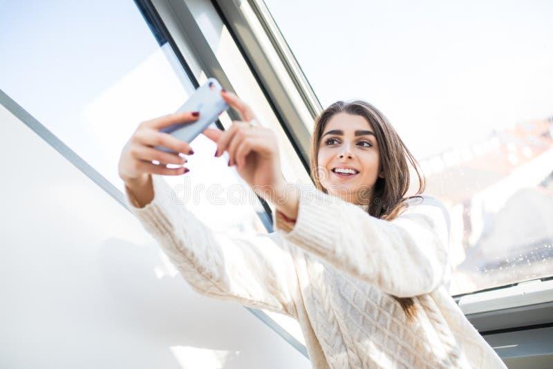 Belle femme caucasienne près de fenêtre, faisant des visages, souriant et faisant à selfie le matin photographie stock