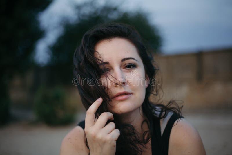 Belle femme châtain dans le T-shirt noir contre le ciel bleu photos stock