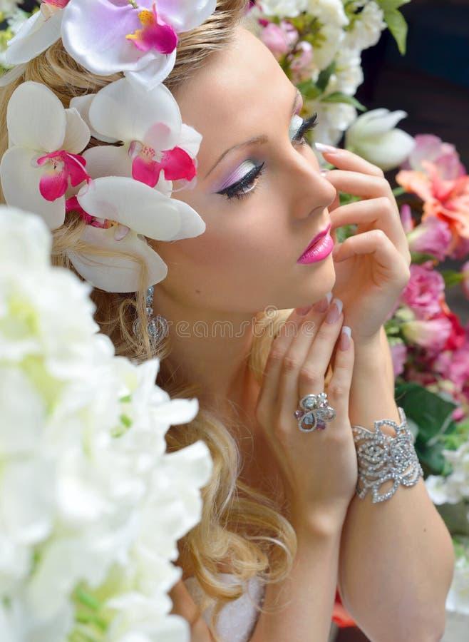 Belle femme chic autour des fleurs. photographie stock