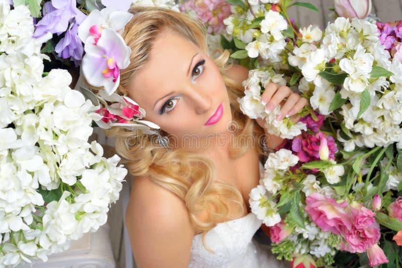 Belle femme chic autour des fleurs. photos stock