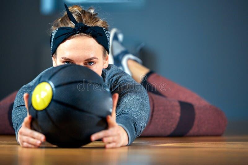 Belle femme convenable dans les vêtements de sport posant tout en se trouvant sur le plancher avec le basket-ball devant la fenêt photographie stock libre de droits