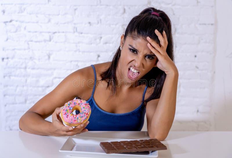 Belle femme convenable suivante un régime rejetant le chocolat et des beignets photos libres de droits
