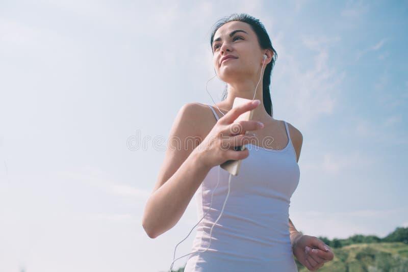 Belle femme courant pendant le coucher du soleil Jeune modèle de forme physique près de bord de la mer Habillé dans les vêtements photo libre de droits