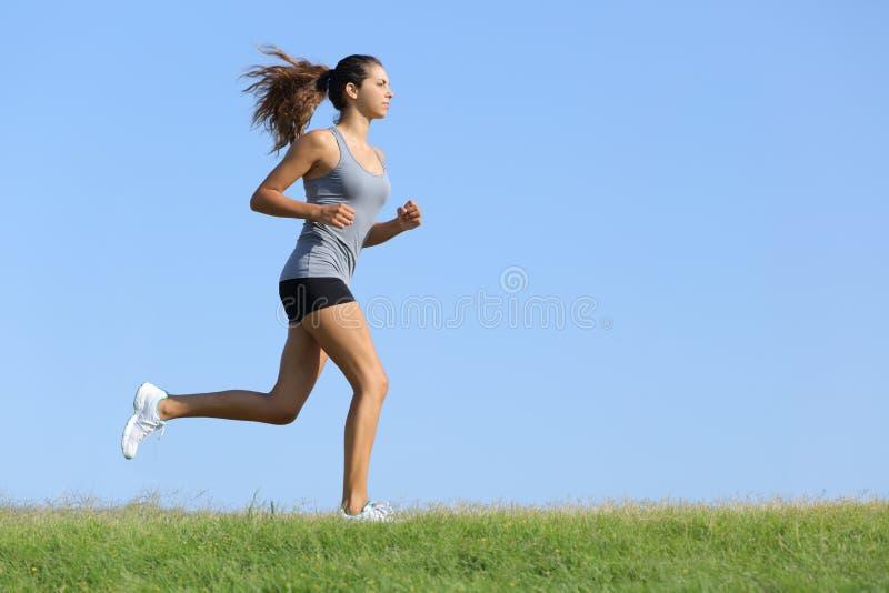 Belle femme courant sur l'herbe avec le ciel à l'arrière-plan photographie stock libre de droits