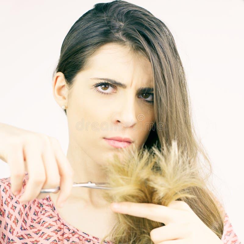 Belle femme décidant de couper des cheveux de pointes fourchues regardant l'appareil-photo d'isolement photo stock