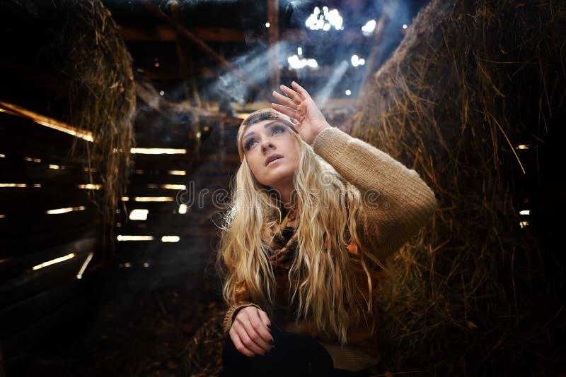 Belle femme détendant en paille en automne dans la chambre fumeuse images libres de droits
