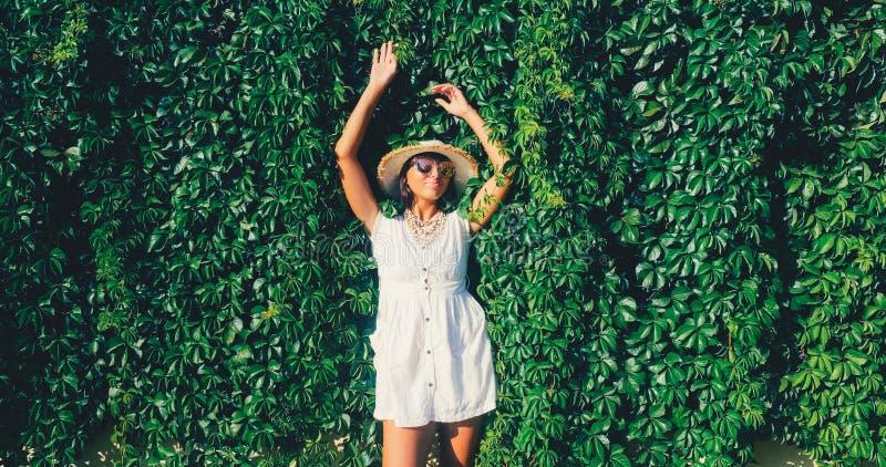 Belle femme détendant sur le fond sauvage de mur de raisin images stock