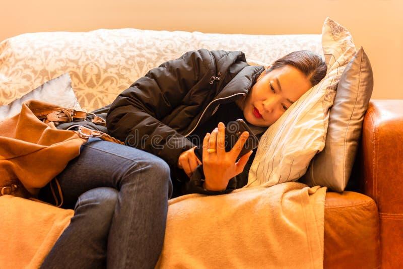 Belle femme détendue utilisant le téléphone intelligent se trouvant sur un sofa dans le salon photographie stock libre de droits