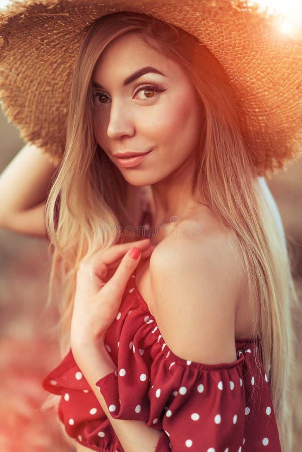 Belle femme d'été dans le domaine de blé, dans une robe rouge, dans un chapeau de paille, cheveux en gros plan et longs Yeux sens photos stock
