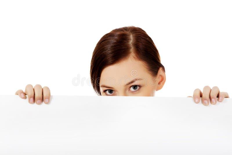 Belle femme d'étudiant cachant son visage derrière la bannière vide images stock