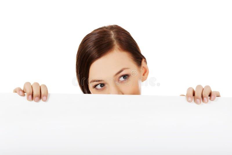 Belle femme d'étudiant cachant son visage derrière la bannière vide photographie stock